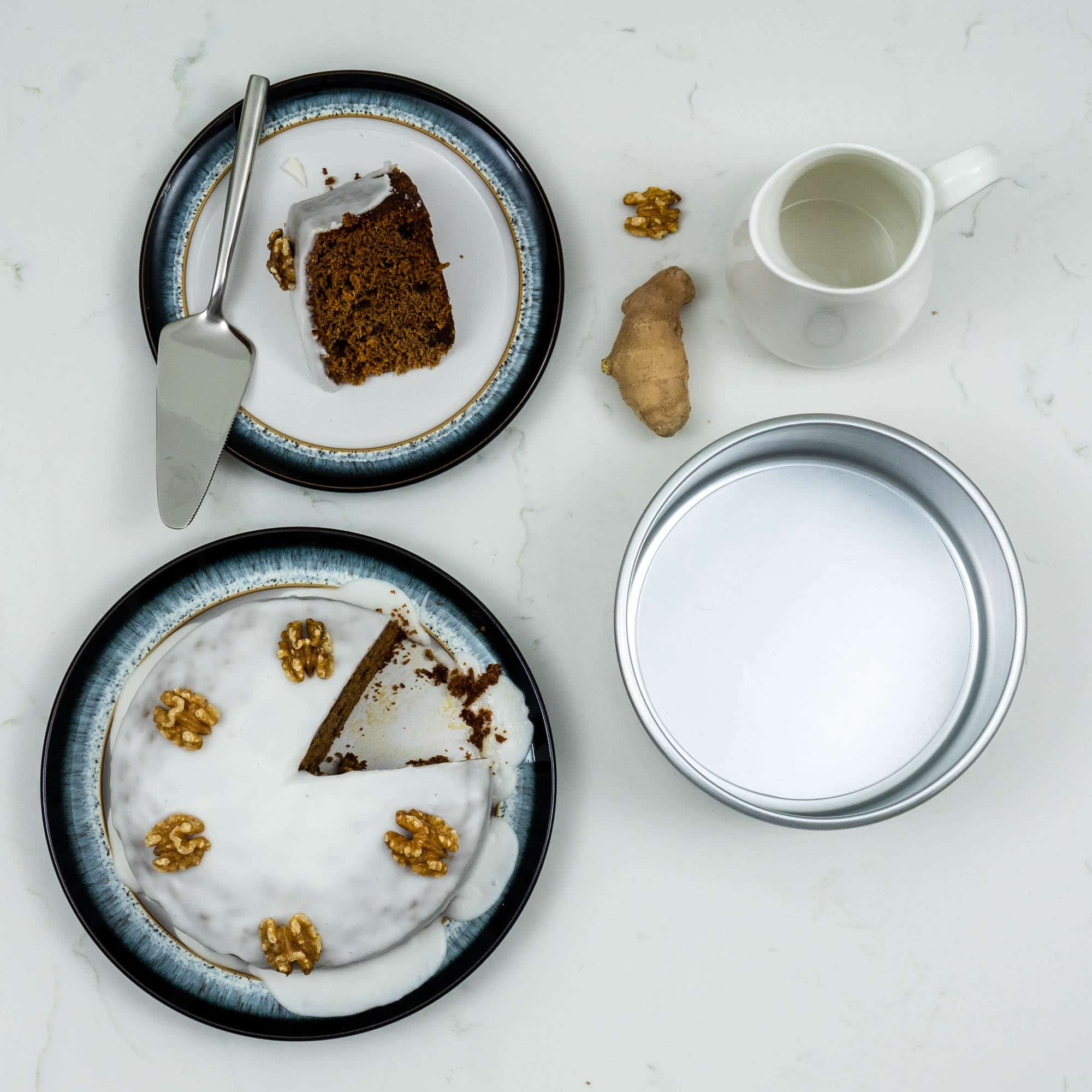 walnut and ginger cake on a plate with slice cut out and tin to the side