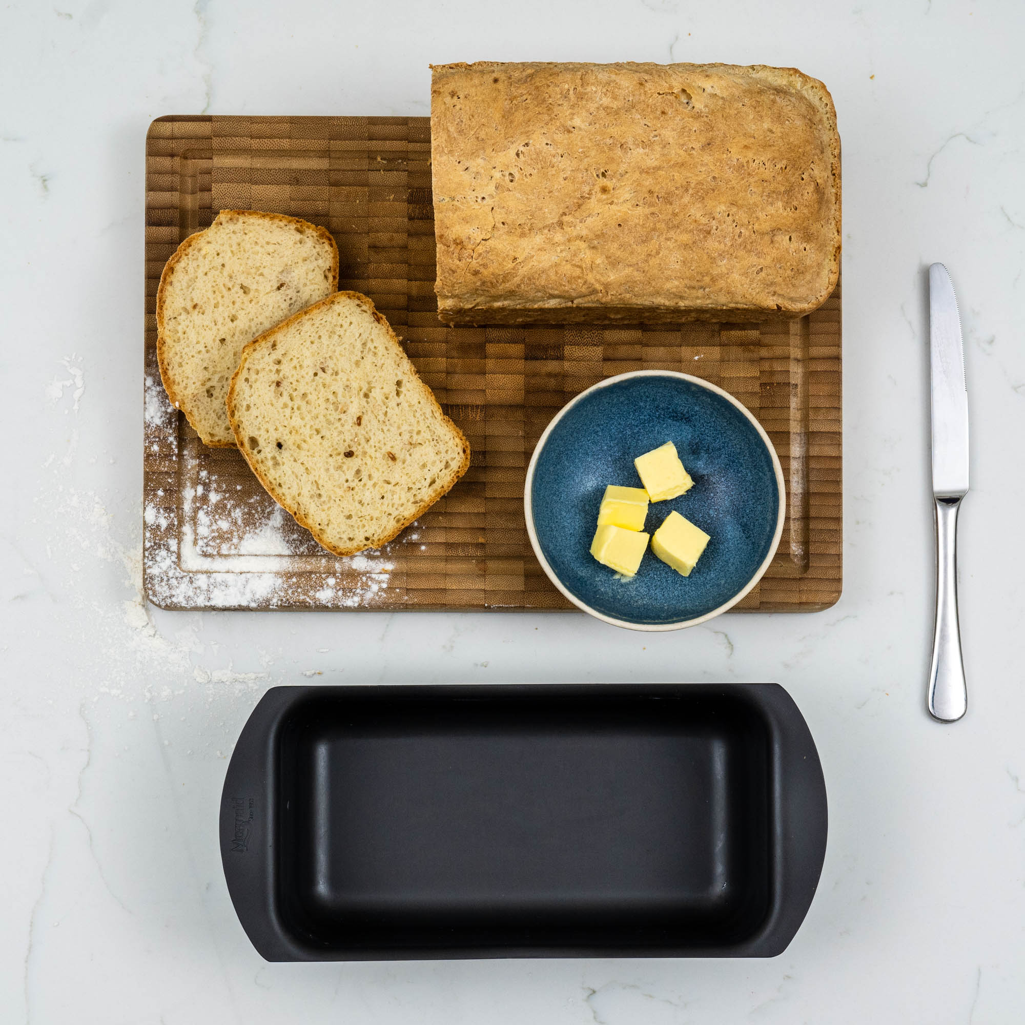 loaf of bread with slices cut off, a bowl of butter and the tin just in front