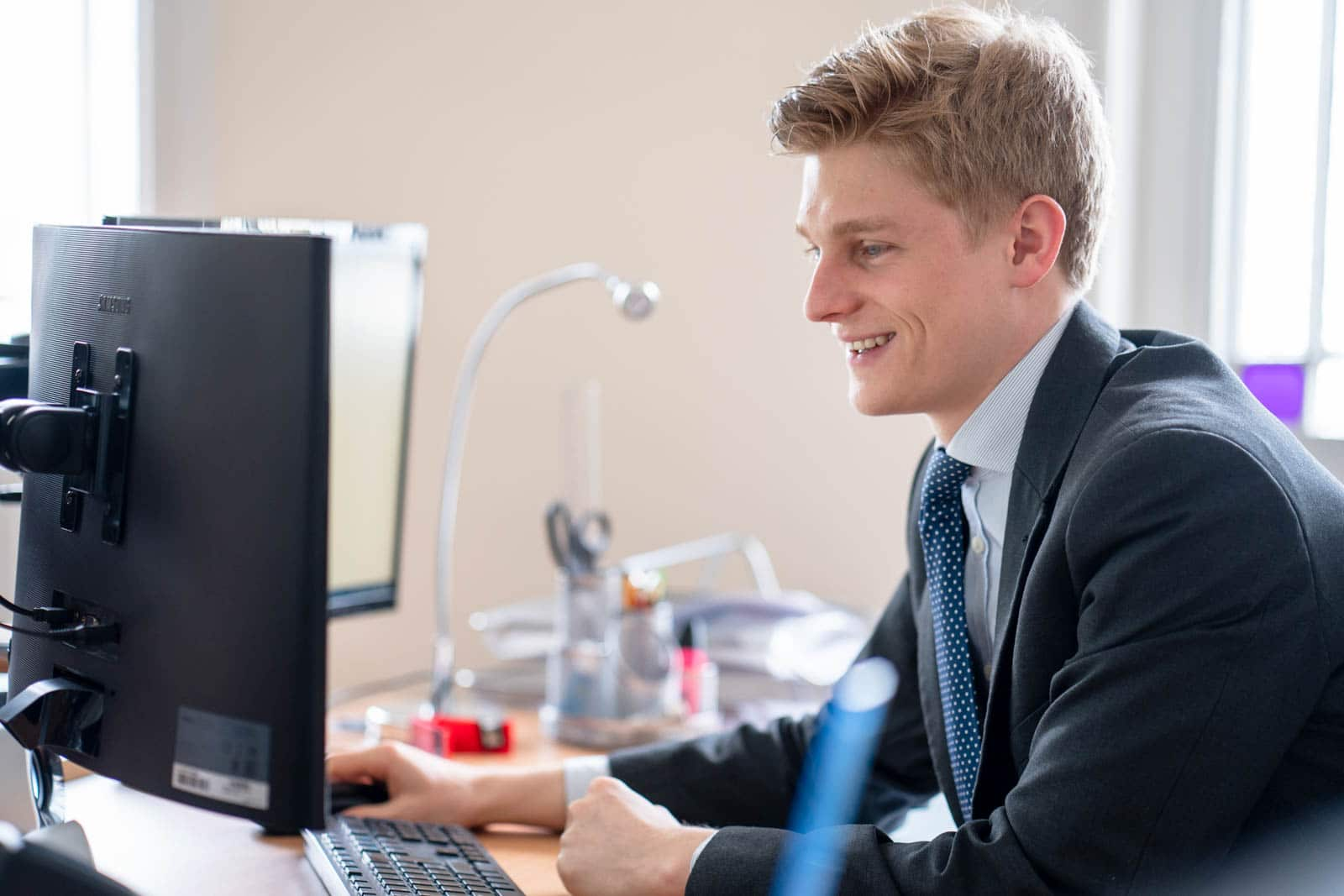 man in suit sat at a desk smiling at the computer screen