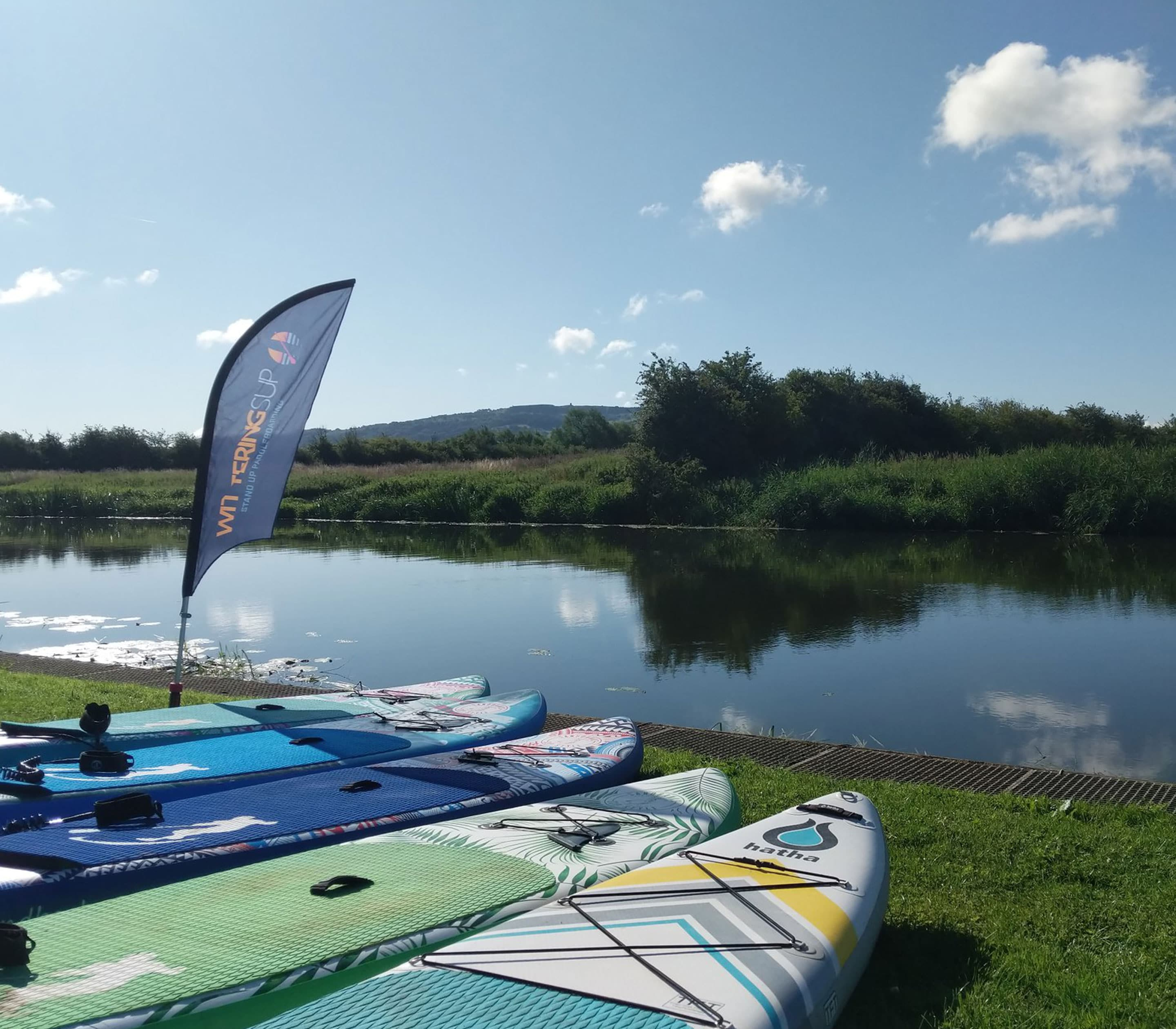 river side, with paddle boards and small wittering sup flag