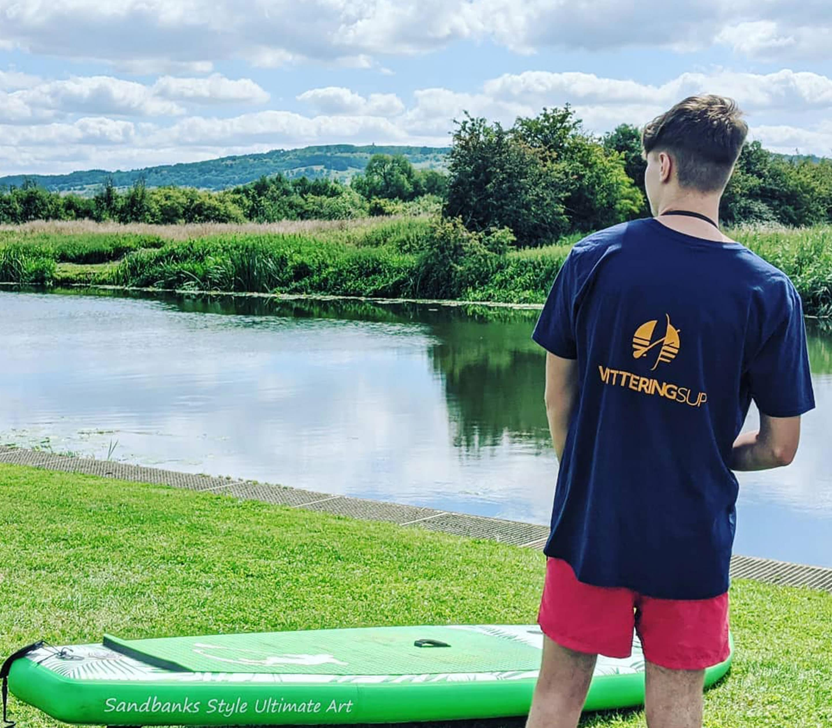 boy in front of river with blue tshirt with orange wittering sup logo on